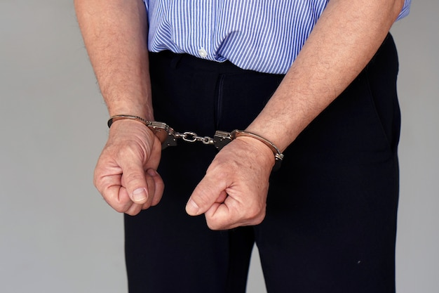 Criminele blanke handen opgesloten in handboeien. close-up bekijken.