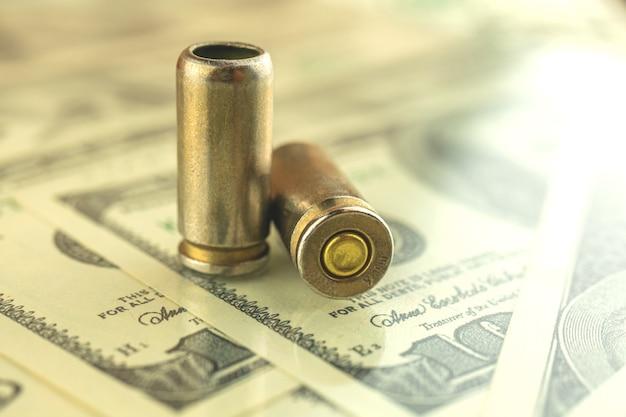 Criminele geldachtergrond met dollarbankbiljetten en kogel voor pistool, 9 mm patroon voor pistool, maffia en corruptiefoto