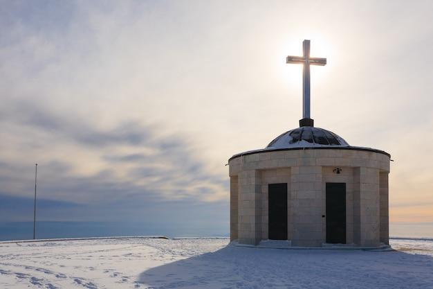 Cristian steekt over een kleine kerk met zon in tegenlicht italiaans winterpanorama