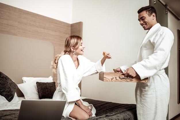 Croissant als ontbijt. vrolijke vrouw die wat croissant als ontbijt neemt terwijl ze met haar man in het hotel woont