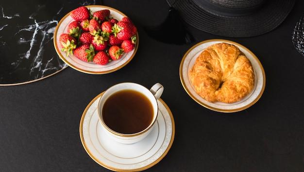 Croissant en aardbeien met thee op tafel