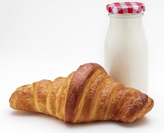 Croissant en fles melk bij het ontbijt