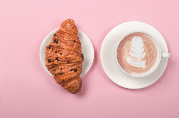 Croissant en kopje koffie op roze achtergrond, bovenaanzicht