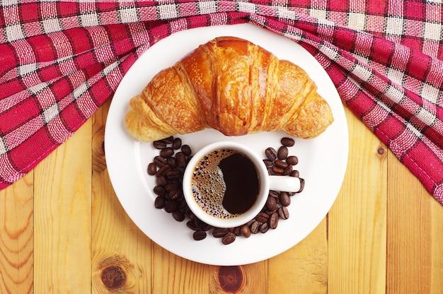Croissant en kopje koffie op tafel