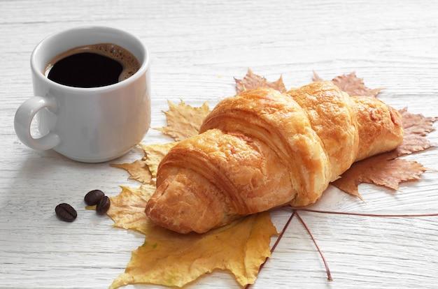 Croissant en kopje warme koffie op witte houten tafel met herfstbladeren