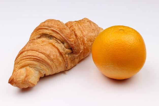 Croissant en sinaasappel op een wit