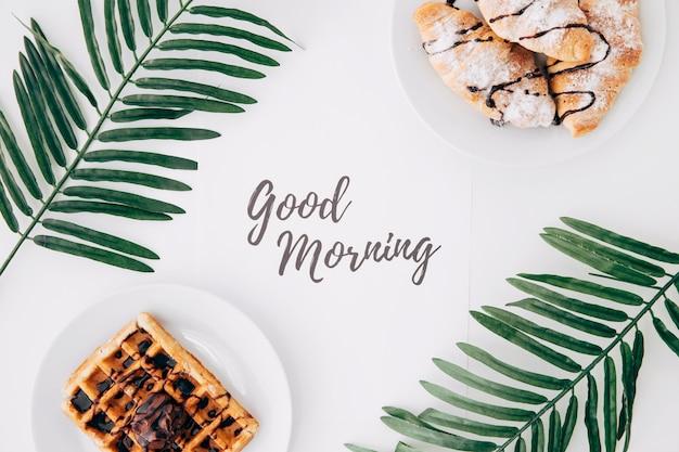 Croissant en wafels met goedemorgentekst en palmbladen op wit bureau Premium Foto