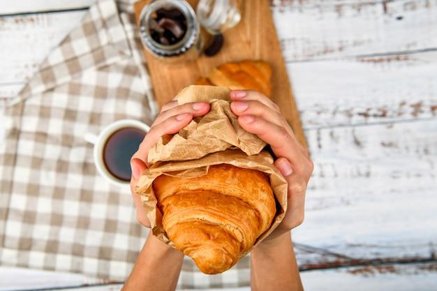 Croissant in de handen. close-up van lekker croissant in de handen. over een flat. verpakt ambachtelijk papier