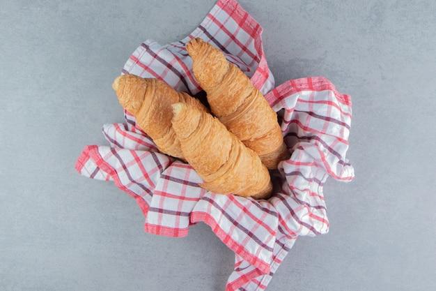 Croissant in de kom op handdoek, op de marmeren achtergrond. hoge kwaliteit foto