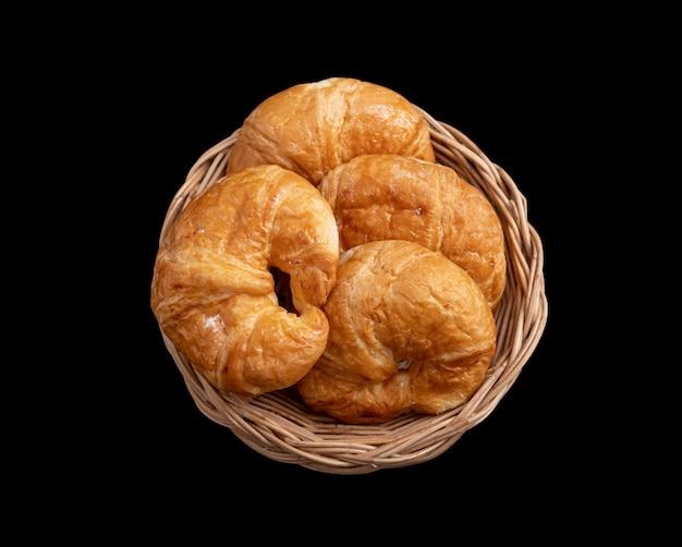 Croissant in de rieten mand op zwart