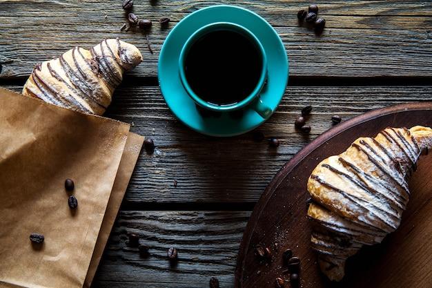 Croissant in een papieren zak met een kopje koffie. ontbijt, snack,