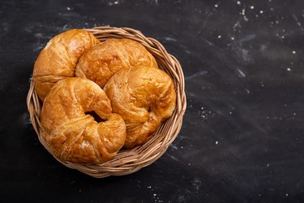 Croissant in een rieten mand op een zwarte vloer