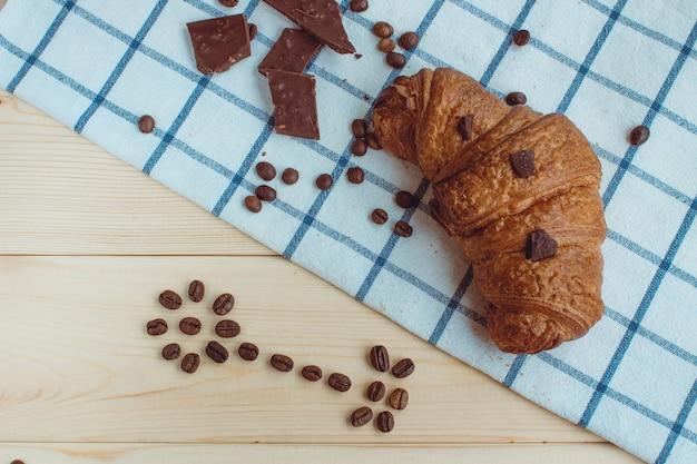 Croissant, koffiebonen en chocolade op een keukenservet en op een houten achtergrond. het uitzicht vanaf de top.