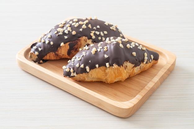 Croissant met chocolade en nootachtig op houten plaat