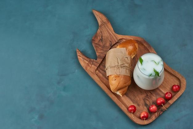 Croissant met een kopje melk en kersen.