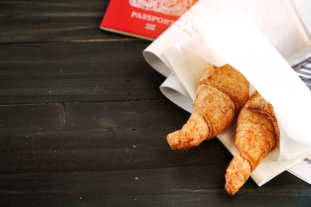 Croissant met het plannen van vakantiereis en klaar om te gaan, gemakkelijk eten tijdens de vlucht voor op reis en jour, neybreakfast de geweldige ochtend is klaar voor een menselijk druk leven in de moderne wereld.