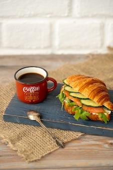 Croissant met komkommer, sla en zalmsandwich met kopje koffie op blauw houten bureau
