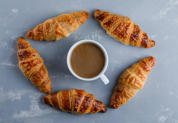 Croissant met kop koffie, plat lag.