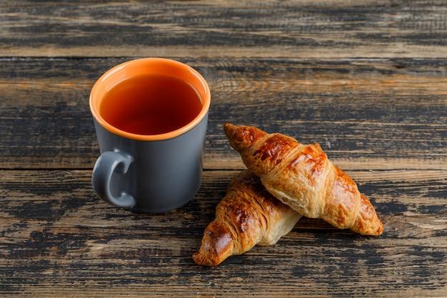 Croissant met kop thee op houten lijst, hoge hoekmening.