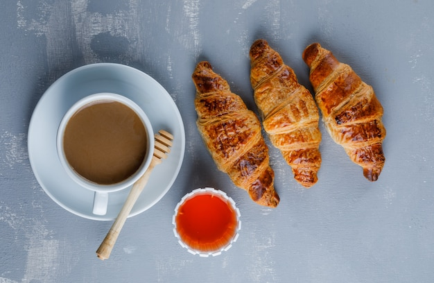 Croissant met kopje koffie, honing, beer, bovenaanzicht.