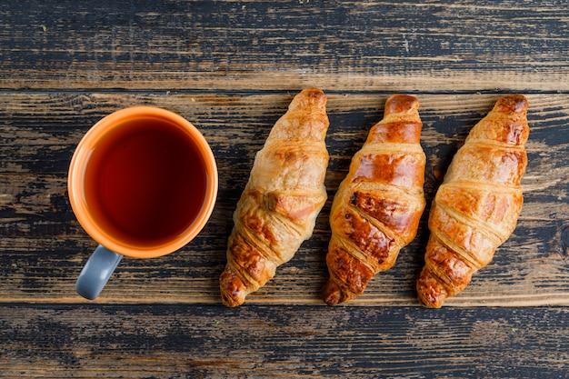 Croissant met kopje thee op houten tafel, plat lag.