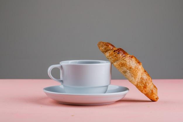 Croissant met kopje thee op roze en grijze tafel, zijaanzicht.