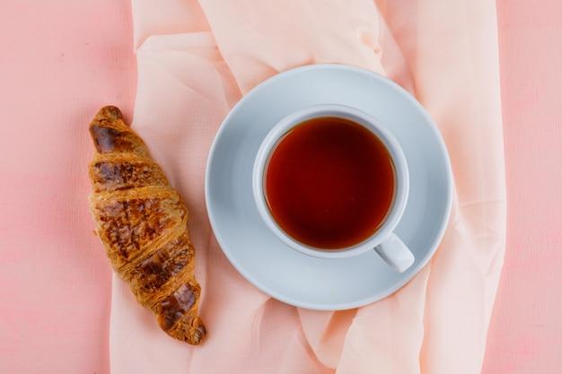 Croissant met kopje thee plat lag