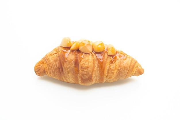 Croissant met macadamia en karamel op een witte achtergrond