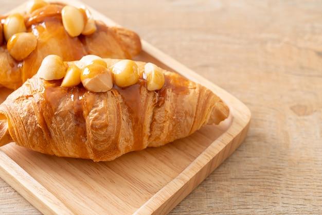 Croissant met macadamia en karamel op houten plaat