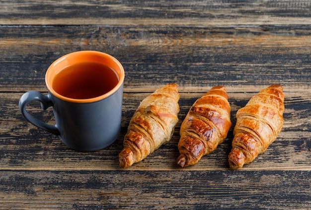 Croissant met mening van de kop thee de hoge hoek over een houten lijst
