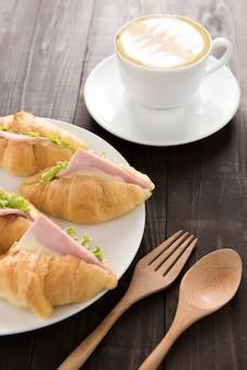 Croissant met parmaham en koffie op houten tafel