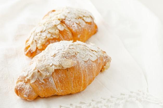 Croissant met poedersuiker en amandelschilfers op witte achtergrond