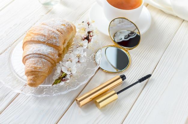 Croissant met thee. mascara voor de ogen en een kleine cosmetische spiegel