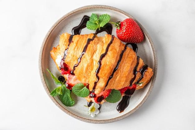 Croissant met verse aardbeien, roomkaas, munt en chocoladesaus voor smakelijk ontbijt op witte achtergrond. bovenaanzicht Premium Foto