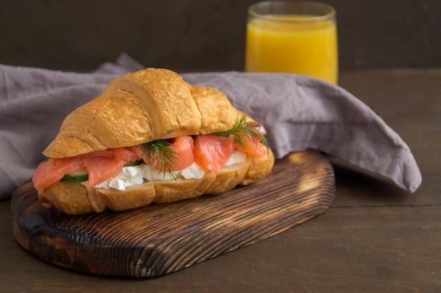 Croissant met zalm en roomkaas op een houten bord.