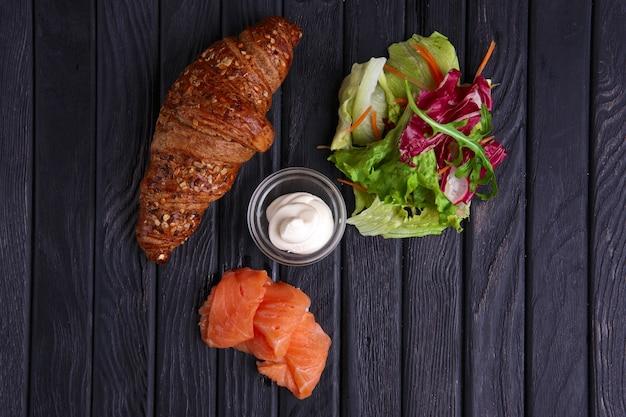 Croissant met zalm, salade en zure room. bovenaanzicht.
