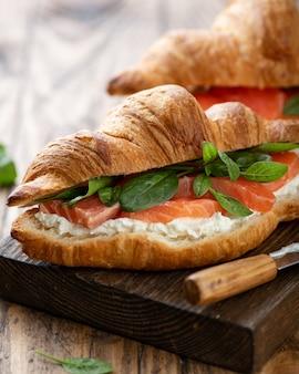 Croissant met zalm, spinazie en roomkaas op een houten bord, selectieve aandacht, close-up