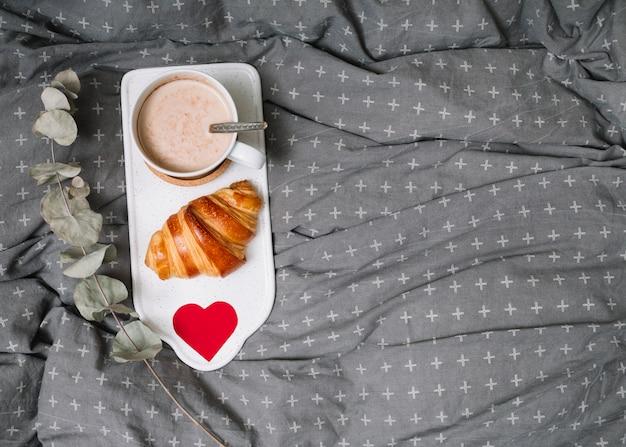 Croissant, ornamenthart en kop van drank op scherpe raad dichtbij takje