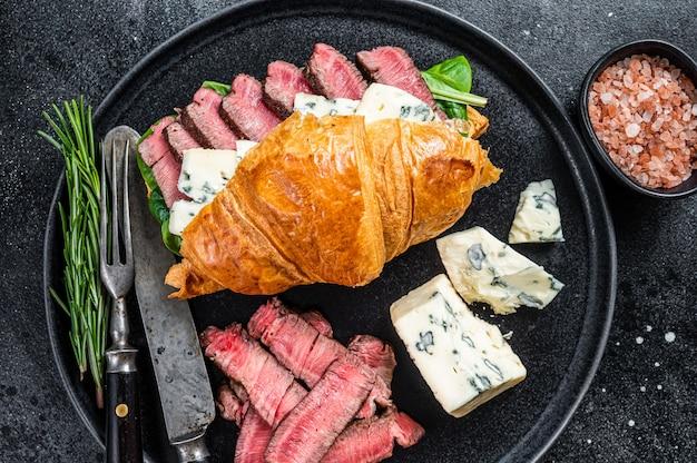 Croissant sandwich met filet mignon ossenhaas vlees steak met blauwe kaas. zwarte achtergrond. bovenaanzicht.