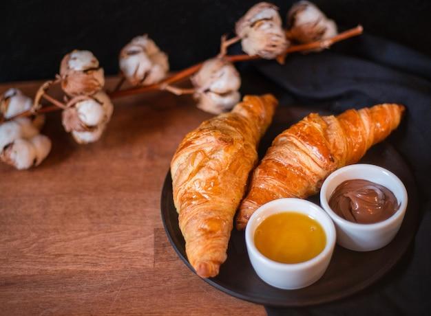 Croissants, chocolade en honing op een donkere achtergrond. houten bord met heerlijk ontbijt, katoenen bloem, bovenaanzicht, plat leggen