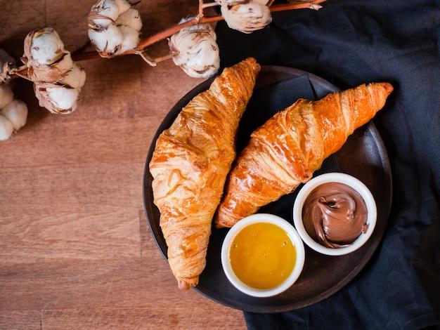 Croissants, chocolade en honing op een donkere achtergrond. houten bord met heerlijk ontbijt, katoenen bloem. bovenaanzicht