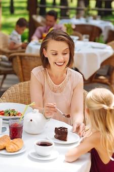 Croissants en brownie. stralende gelukkige moeder en dochter die heerlijke croissants en brownie buiten eten
