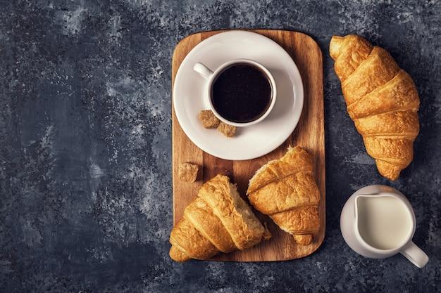 Croissants en koffie op een donkere tafel