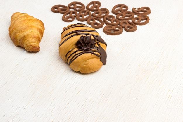 Croissants en krullende koekjes op witte achtergrond. bovenaanzicht. kopieer ruimte