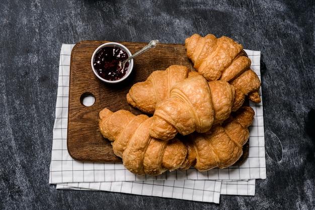Croissants en pot met jam opzij op grijze tafel