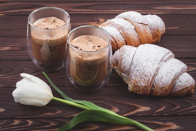 Croissants en twee glazen schuimige koffie op een donkerbruine houten tafel. frans ontbijtconcept, pauze. drankjes en snoep, bladerdeeg en witte bloem op planken, lente, ochtendtijd.