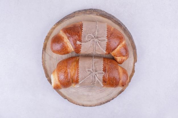 Croissants geïsoleerd op een houten schotel op een grijze ondergrond
