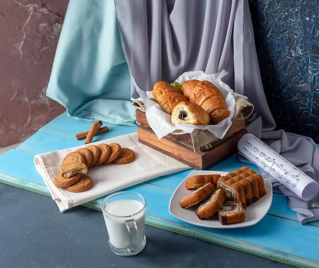 Croissants, gesneden taart en koekjes met een kopje melk.