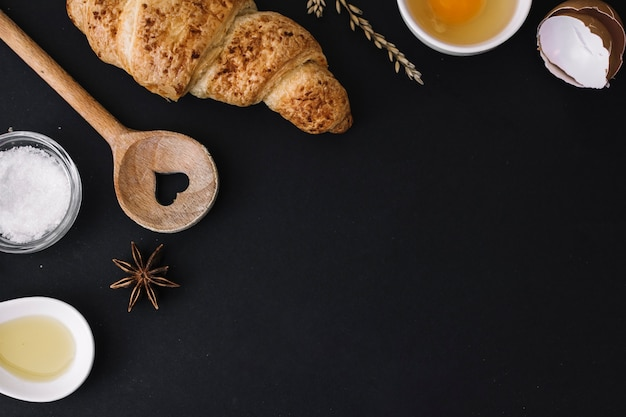 Croissants; houten vormlepel en bakselingrediënten op zwarte achtergrond
