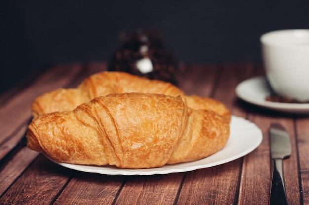 Croissants in een bord een kopje met een drankje een snack van het maaltijddessert. hoge kwaliteit foto
